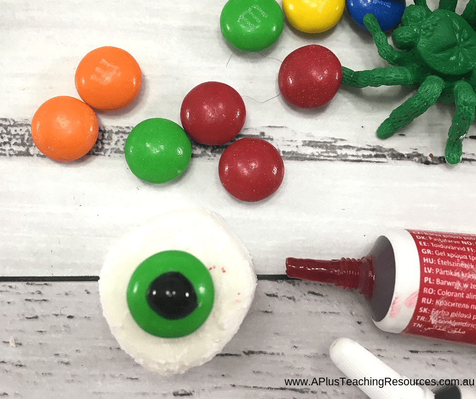 Place m&m on marshmallow eyeball