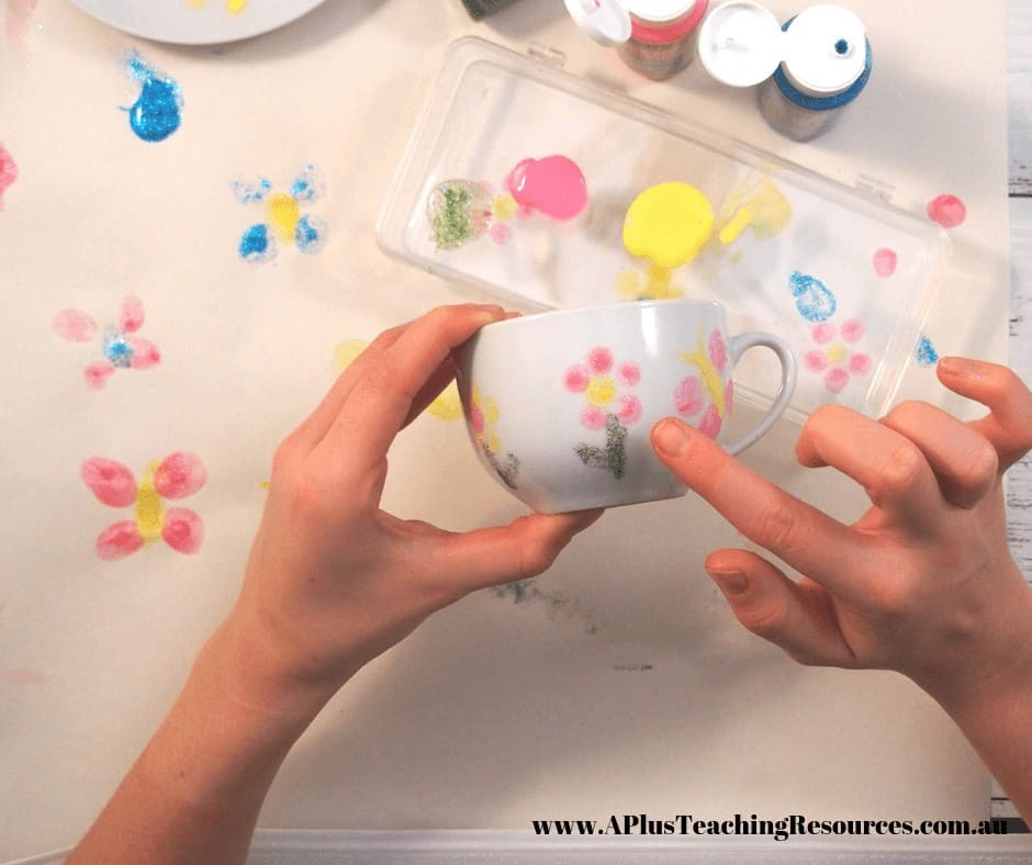Image of gir making fingerprints on a Mothers day tea cup present